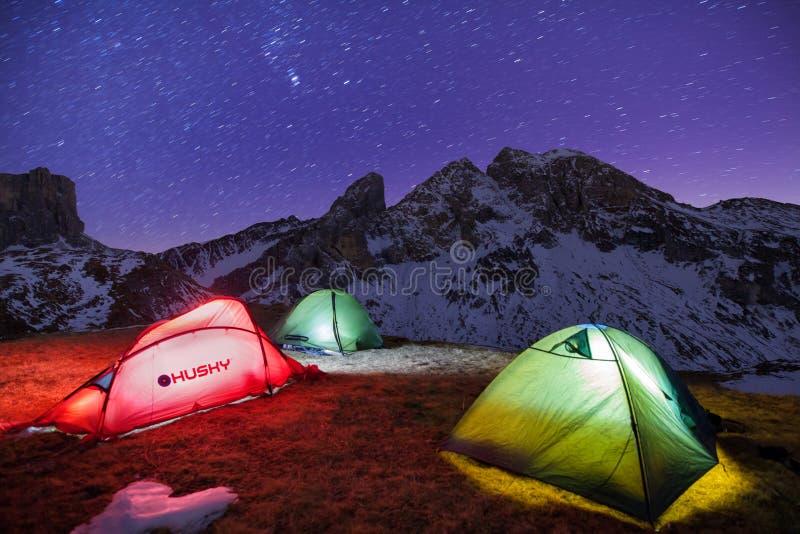 Χειμερινό στρατόπεδο, νύχτα, λάμποντας πράσινη σκηνή στο χιόνι Νύχτα πυροβοληθείσα, μακροχρόνια έκθεση, που κοιμάται στο χιόνι έξ στοκ φωτογραφία με δικαίωμα ελεύθερης χρήσης