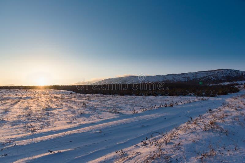 Χειμερινό τοπίο ηλιοβασιλέματος με το χιονισμένο τομέα στοκ φωτογραφίες