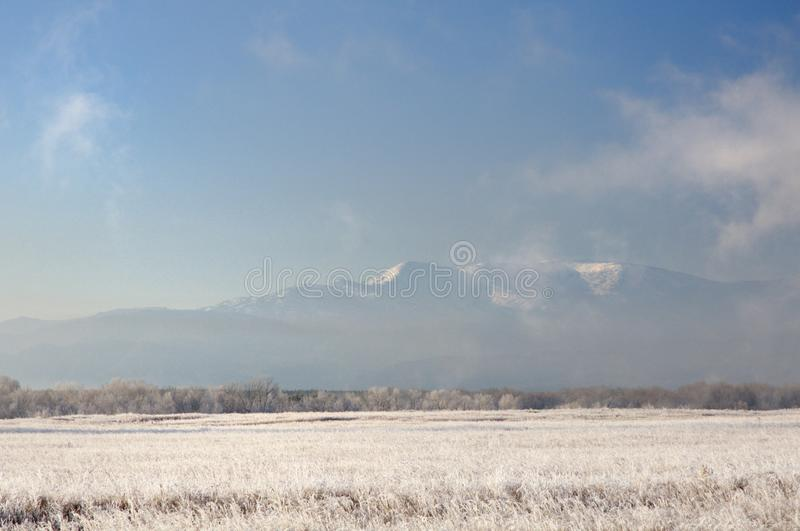 Χειμερινό τοπίο με τα χιονώδη βουνά πίσω από τον τομέα που καλύπτεται με την παγωμένη ξηρά χλόη από το σκούρο μπλε ουρανό κατά τη στοκ εικόνες