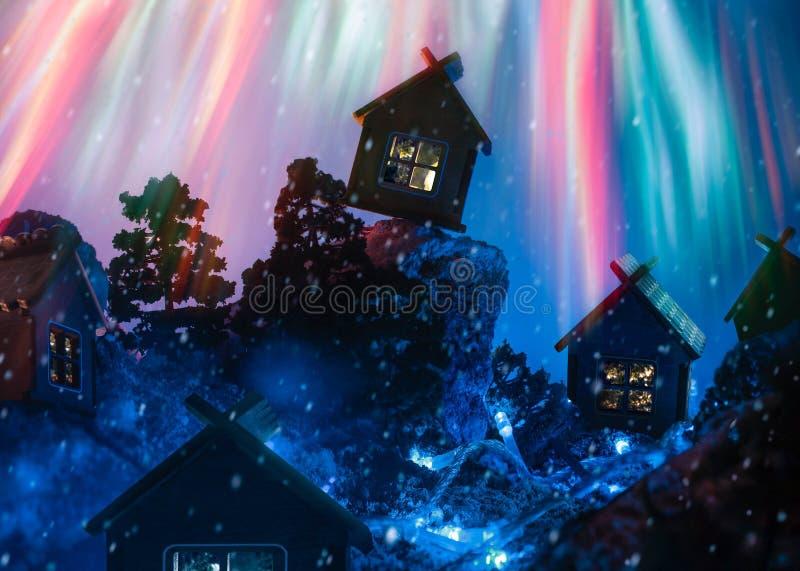 Χειμερινό τοπίο νύχτας με τις καλύβες και τα πυροτεχνήματα στοκ εικόνα