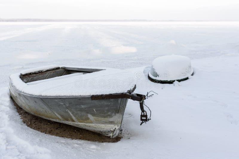 Χειμερινό τοπίο της παγωμένων λίμνης, της ακτής και των βαρκών που καλύπτονται με sn στοκ φωτογραφία με δικαίωμα ελεύθερης χρήσης