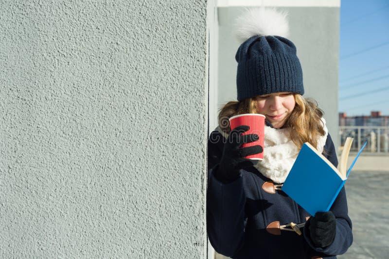 Χειμερινό υπαίθριο πορτρέτο της νέας γυναίκας σπουδαστή με το βιβλίο και το φλυτζάνι, διάστημα αντιγράφων στοκ εικόνες