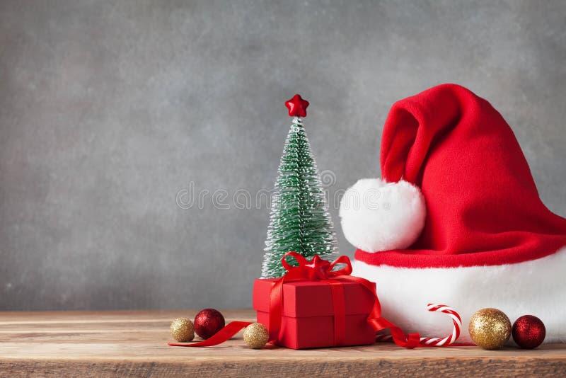 Χειμερινό υπόβαθρο με το δώρο Χριστουγέννων ή το παρόν κιβώτιο, το καπέλο Santa και τις διακοσμήσεις διακοπών χαιρετισμός καλή χρ στοκ εικόνες