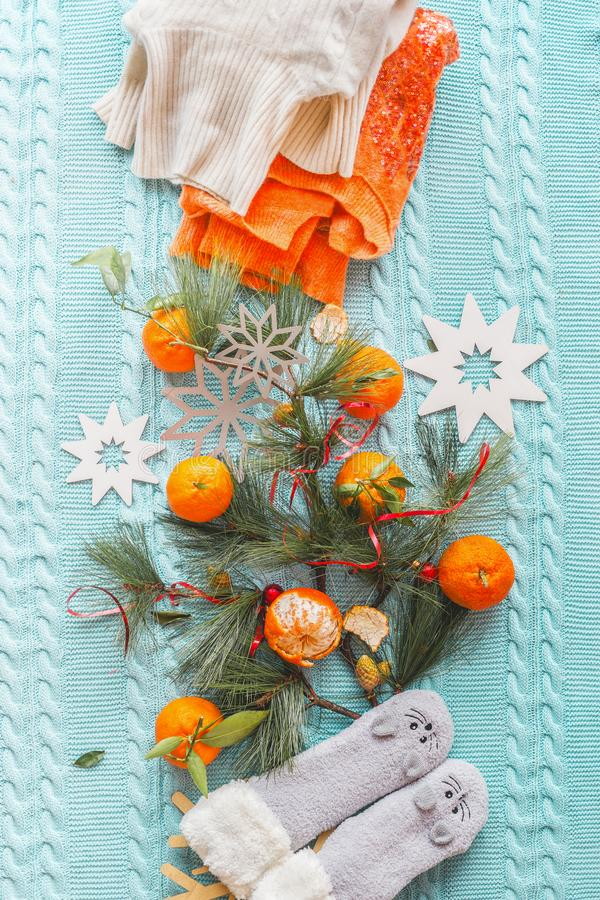 Χειμωνιάτικη διάθεση με tangerines, πορτοκαλί πουλόβερ, αστείες κάλτσες και κλαδιά fir σε μπλε πλεκτή κουβέρτα με νιφάδες χιονιού στοκ φωτογραφία με δικαίωμα ελεύθερης χρήσης