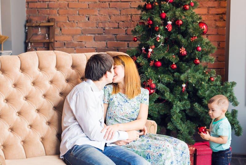 Χειμώνας, ζεύγος, Χριστούγεννα και έννοια ανθρώπων - άνδρας και φίλημα γυναικών πέρα από το υπόβαθρο και το παιδί χριστουγεννιάτι στοκ εικόνες