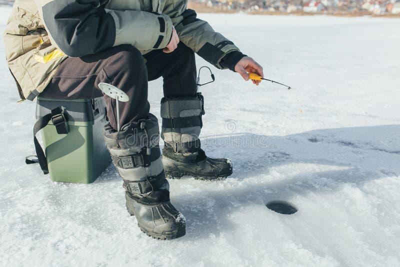 Χειμώνας που αλιεύει, η ράβδος αλιείας στέκεται στην τρύπα που περιμένει τα ψάρια στοκ φωτογραφία