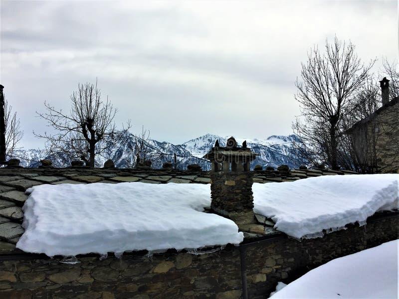 Χειμώνας, χιόνι, στέγη, σωρός καπνοδόχων και βουνά στοκ φωτογραφίες