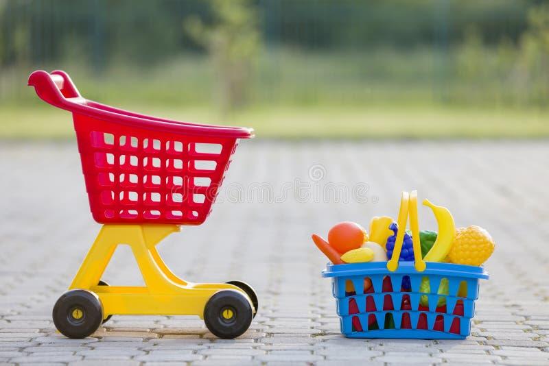 Χειράμαξα αγορών και ένα καλάθι με τα φρούτα και λαχανικά παιχνιδιών Φωτεινά πλαστικά ζωηρόχρωμα παιχνίδια για τα παιδιά υπαίθρια στοκ εικόνα