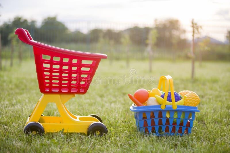 Χειράμαξα αγορών και ένα καλάθι με τα φρούτα και λαχανικά παιχνιδιών Φωτεινά πλαστικά ζωηρόχρωμα παιχνίδια για τα παιδιά υπαίθρια στοκ εικόνες