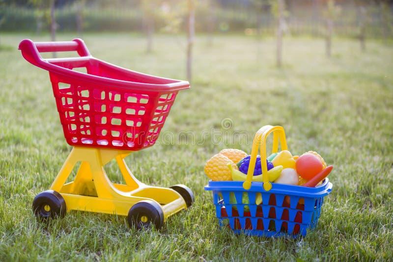 Χειράμαξα αγορών και ένα καλάθι με τα φρούτα και λαχανικά παιχνιδιών Φωτεινά πλαστικά ζωηρόχρωμα παιχνίδια για τα παιδιά υπαίθρια στοκ εικόνα με δικαίωμα ελεύθερης χρήσης