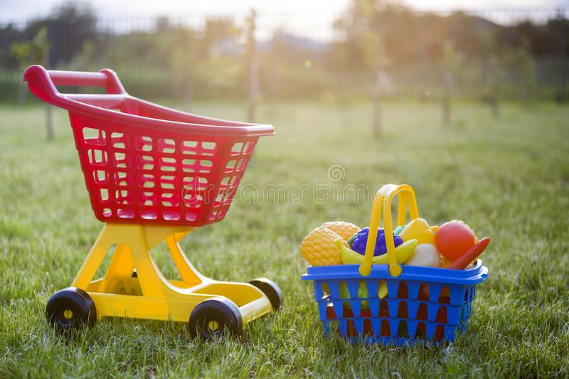 Χειράμαξα αγορών και ένα καλάθι με τα φρούτα και λαχανικά παιχνιδιών Φωτεινά πλαστικά ζωηρόχρωμα παιχνίδια για τα παιδιά υπαίθρια στοκ εικόνες με δικαίωμα ελεύθερης χρήσης
