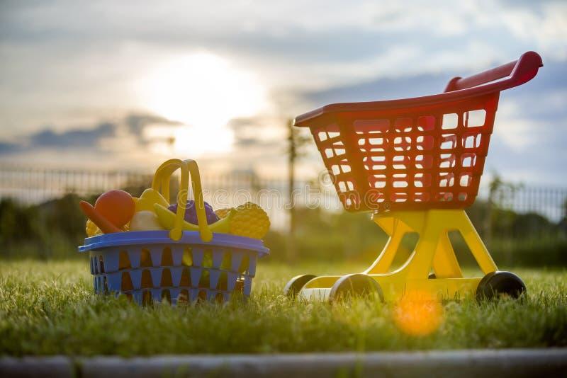 Χειράμαξα αγορών και ένα καλάθι με τα φρούτα και λαχανικά παιχνιδιών Φωτεινά πλαστικά ζωηρόχρωμα παιχνίδια για τα παιδιά υπαίθρια στοκ φωτογραφία με δικαίωμα ελεύθερης χρήσης