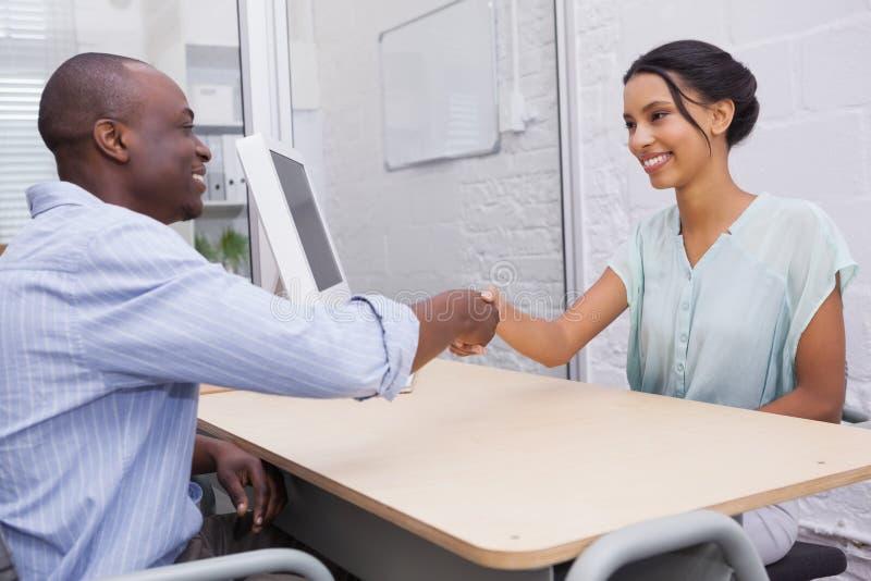 Χειραψία για να σφραγίσει μια διαπραγμάτευση μετά από μια επιχειρησιακή συνεδρίαση στοκ εικόνες
