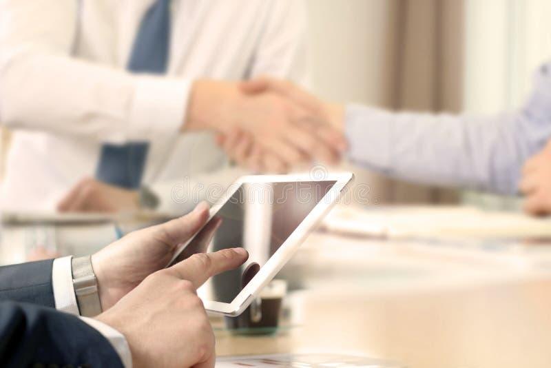 Χειραψία συνέταιρων πέρα από τα επιχειρησιακά αντικείμενα στον εργασιακό χώρο Επιχειρηματίας που εργάζεται με την ψηφιακή ταμπλέτ στοκ εικόνες