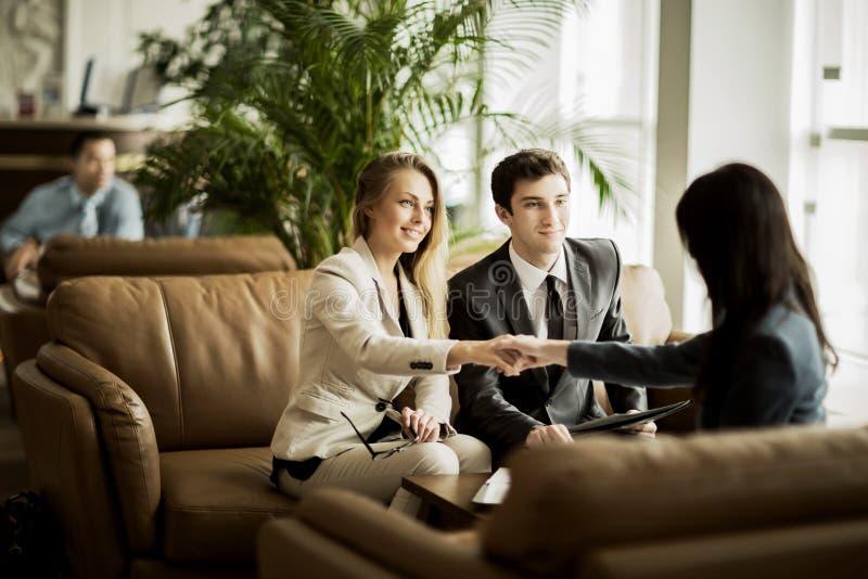 Χειραψία του διευθυντή και του πελάτη μετά από τη συζήτηση συμβάσεων στο λόμπι του σύγχρονου γραφείου στοκ φωτογραφία με δικαίωμα ελεύθερης χρήσης