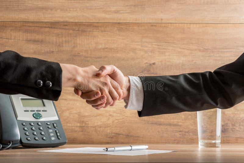 Χειραψία των συνέταιρων επάνω από μια γραπτή συμφωνία στοκ φωτογραφία