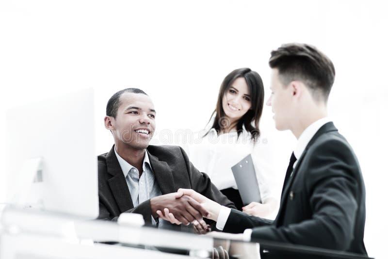 Χειραψία των συνέταιρων που κάθονται σε ένα επιτραπέζιο γραφείο στοκ εικόνες