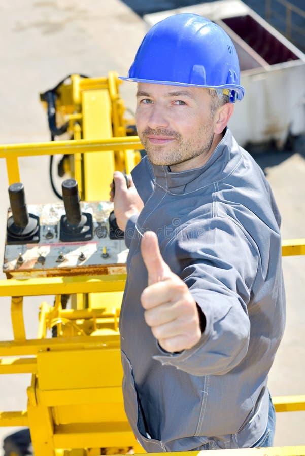Χειριστής γερανών στο εργοτάξιο οικοδομής που φαίνεται ευτυχής στοκ φωτογραφίες