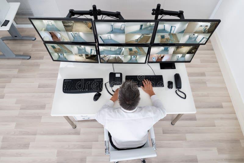 Χειριστής συστημάτων ασφαλείας που εξετάζει το μήκος σε πόδηα CCTV στο γραφείο στοκ εικόνες με δικαίωμα ελεύθερης χρήσης