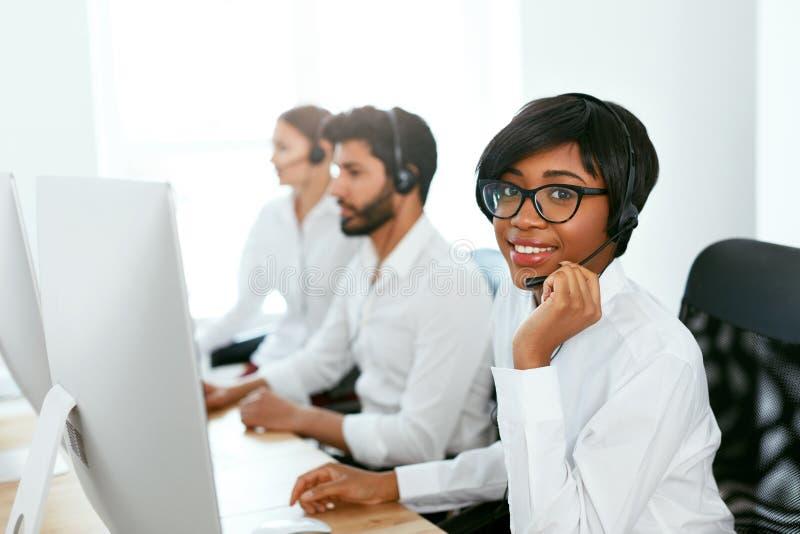 Χειριστής τηλεφωνικών κέντρων με τους συναδέλφους στον εργασιακό χώρο στοκ εικόνα