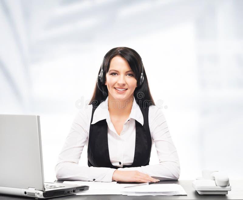 Χειριστής υποστήριξης πελατών που εργάζεται σε ένα γραφείο τηλεφωνικών κέντρων στοκ εικόνα