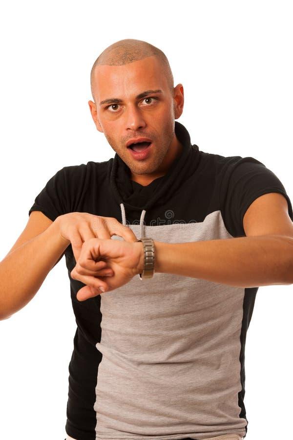 Χειρονομία νεαρών άνδρων που είναι αργά προσέχοντας στο ρολόι που απομονώνεται πέρα από το whi στοκ φωτογραφία