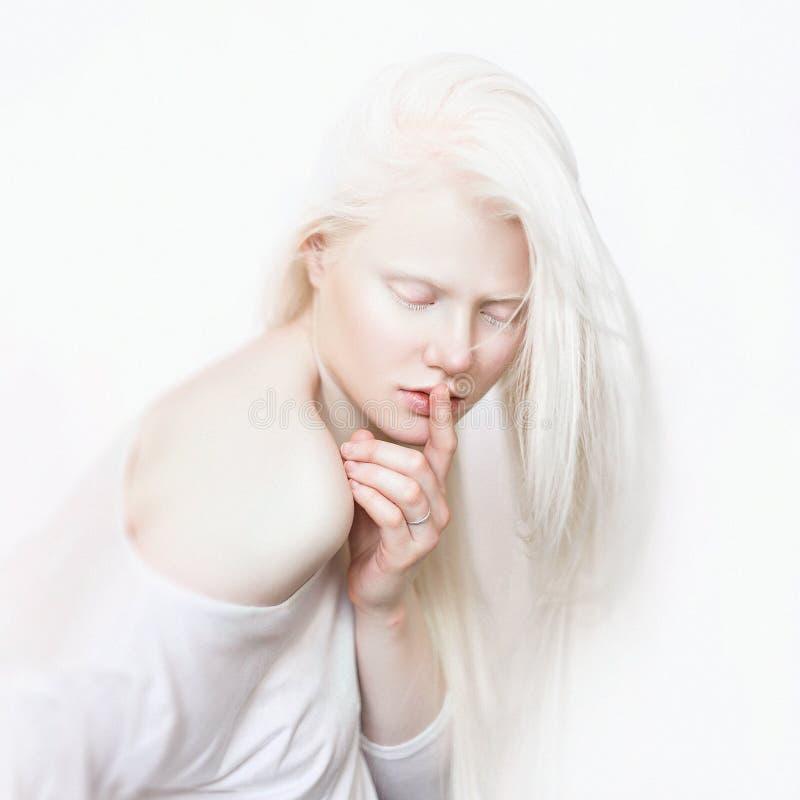 Χειρονομία Shhh Albino θηλυκό με το άσπρο δέρμα και άσπρο μακρυμάλλη Πρόσωπο φωτογραφιών σε ένα ελαφρύ υπόβαθρο Ξανθό κορίτσι στοκ εικόνα