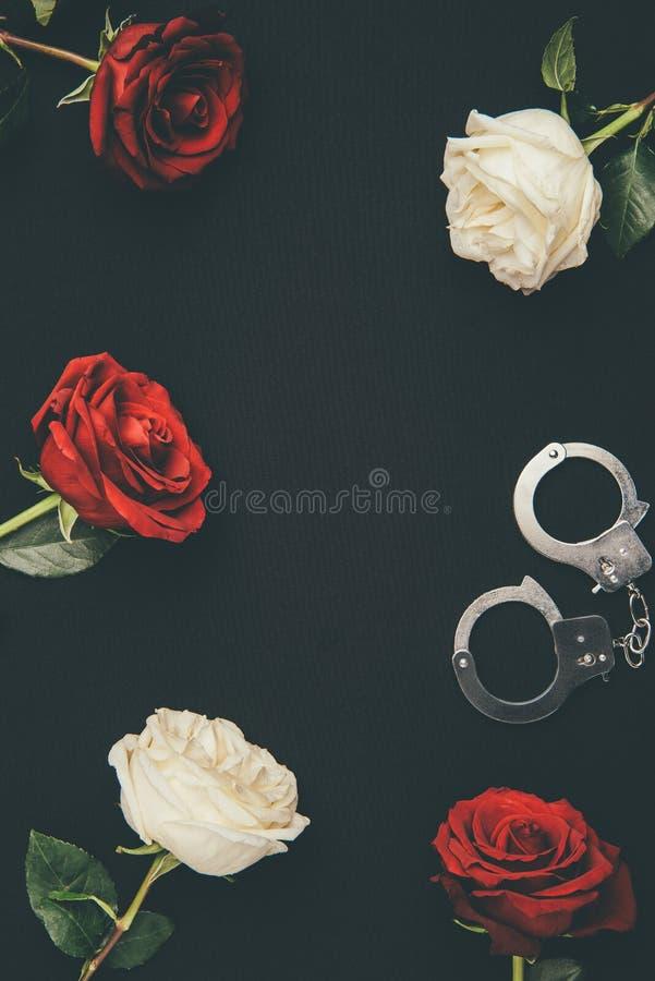 Χειροπέδες μετάλλων με τα ροδαλά λουλούδια στοκ φωτογραφίες με δικαίωμα ελεύθερης χρήσης