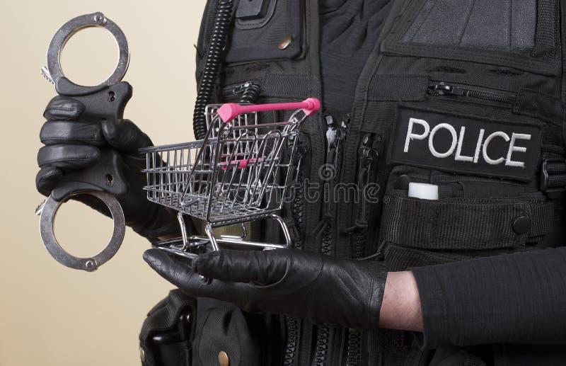 Χειροπέδες αστυνομίας και ένα καροτσάκι υπεραγορών στοκ φωτογραφία