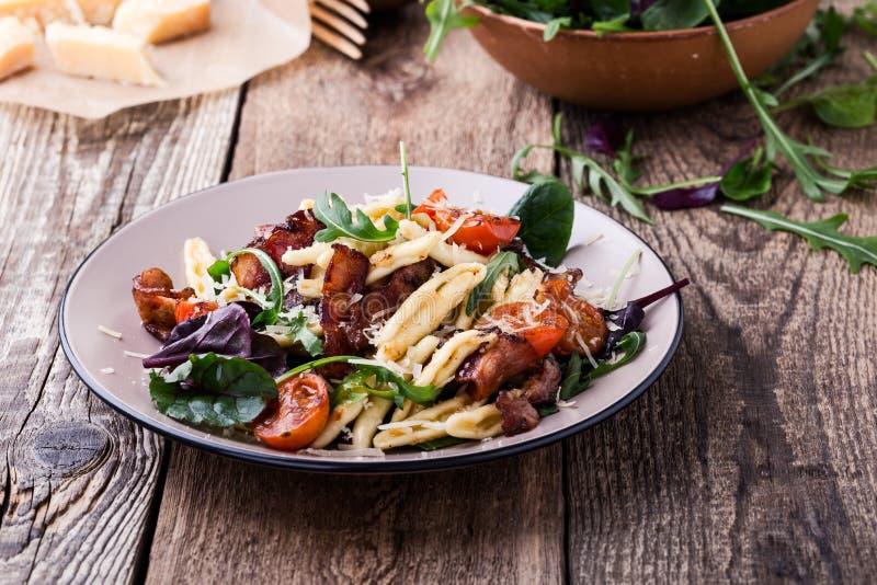 Χειροποίητα ζυμαρικά fusilli με το pancetta, τις ψημένες ντομάτες κερασιών και τα φρέσκα πράσινα λαχανικά στοκ εικόνες