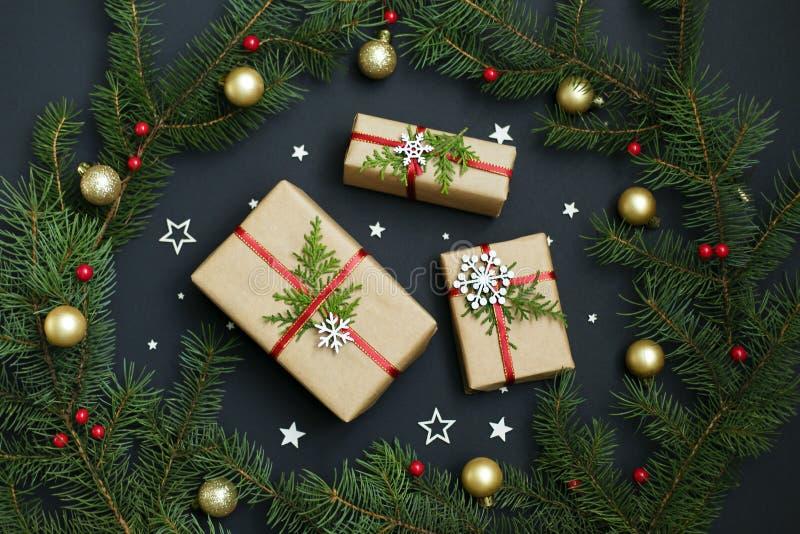 Χειροποίητα κιβώτια δώρων Χριστουγέννων που διακοσμούνται με το έγγραφο τεχνών και άσπρα snowflakes στη σκοτεινή τοπ άποψη υποβάθ στοκ εικόνες