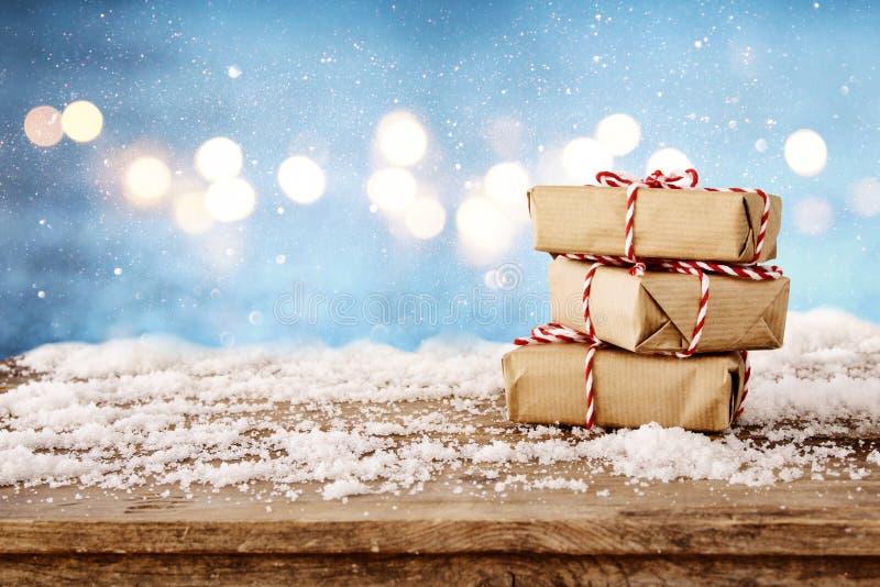 χειροποίητα κιβώτια δώρων πέρα από το χιονώδη ξύλινο πίνακα στοκ φωτογραφία