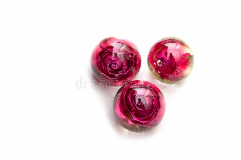 Χειροποίητα κοσμήματα με εποξειδική ρητίνη τριαντάφυλλα στη σφαίρα, τρία κομμάτια προβολή επάνω αποξηραμένα άνθη βότανο, oshibana στοκ εικόνες