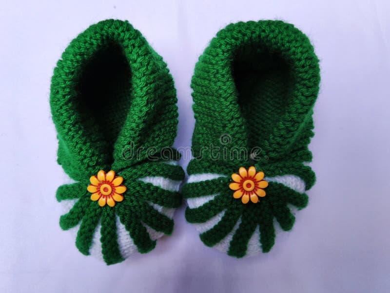 Χειροποίητα πράσινα και άσπρα μάλλινα παπούτσια για το μωρό στοκ εικόνες