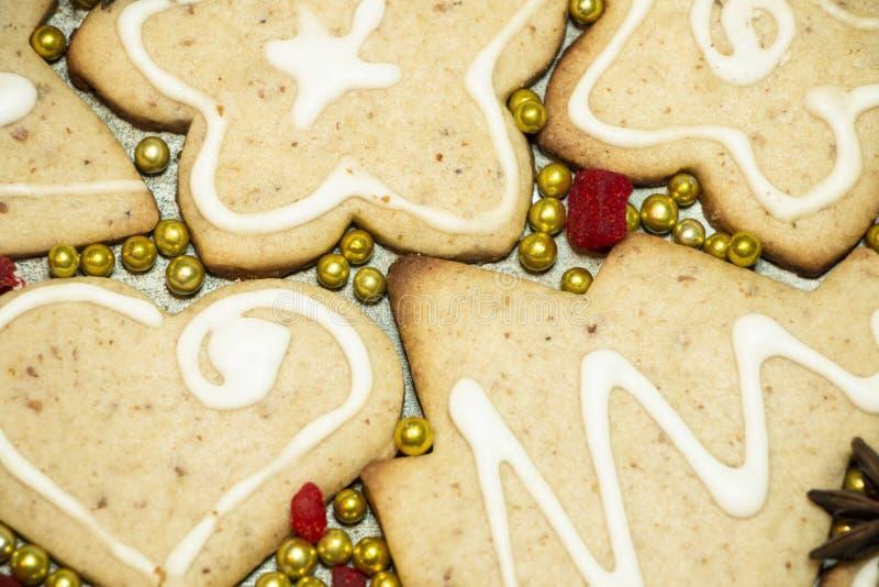 Χειροποίητα χριστουγεννιάτικα μπισκότα με λευκό υαλοστάσιο, χρυσές μα στοκ εικόνες