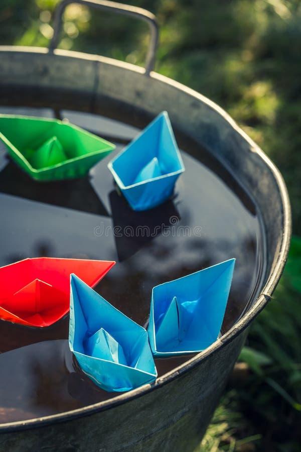 Χειροποίητες βάρκες εγγράφου χρώματος στο νερό ως έννοια ταξιδιού στοκ εικόνες