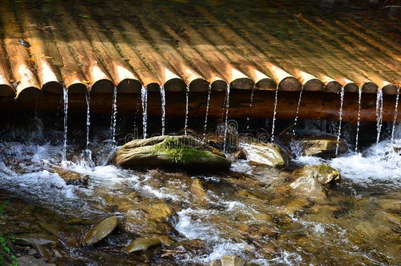 Χειροποίητοι ξύλινοι αγωγοί νερού από τις μικρές αντιμετωπισμένες ακτίνες Ένα όμορφο τεμάχιο ενός μικρού καταρράκτη στοκ εικόνες