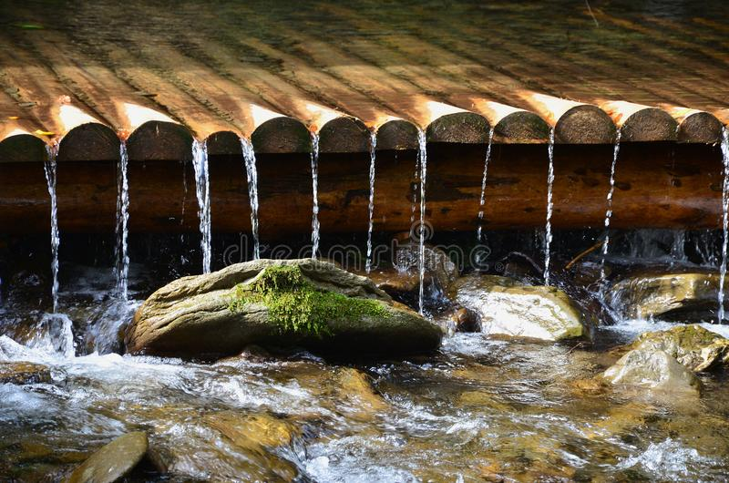 Χειροποίητοι ξύλινοι αγωγοί νερού από τις μικρές αντιμετωπισμένες ακτίνες Ένα όμορφο τεμάχιο ενός μικρού καταρράκτη στοκ φωτογραφία με δικαίωμα ελεύθερης χρήσης