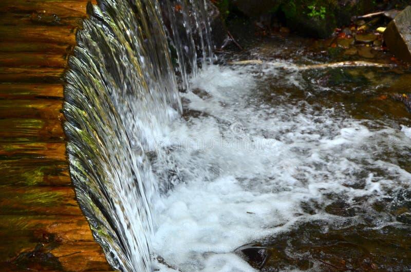 Χειροποίητοι ξύλινοι αγωγοί νερού από τις μικρές αντιμετωπισμένες ακτίνες Ένα όμορφο τεμάχιο ενός μικρού καταρράκτη στοκ εικόνα με δικαίωμα ελεύθερης χρήσης