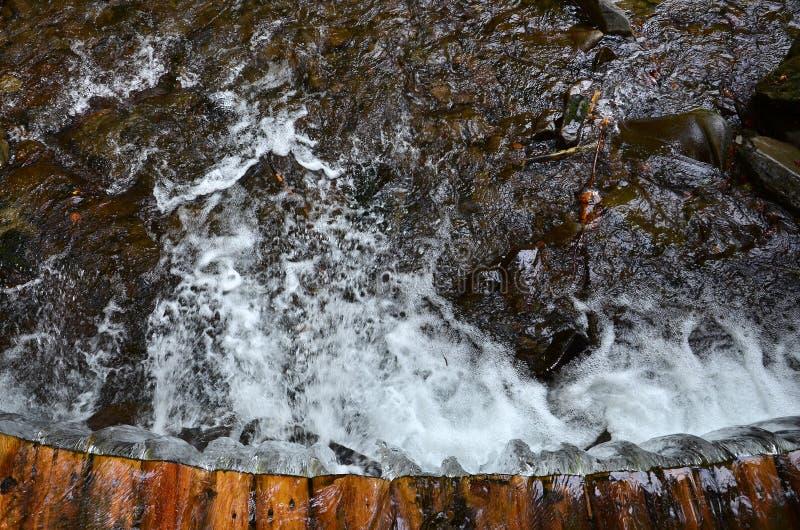 Χειροποίητοι ξύλινοι αγωγοί νερού από τις μικρές αντιμετωπισμένες ακτίνες Ένα όμορφο τεμάχιο ενός μικρού καταρράκτη στοκ φωτογραφίες με δικαίωμα ελεύθερης χρήσης