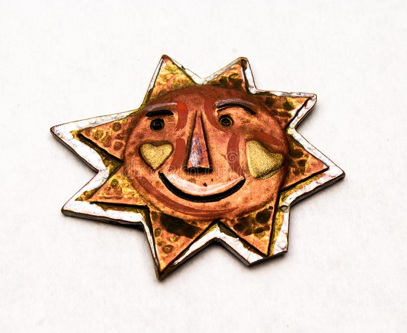 Χειροποίητος ήλιος χαλκού και μετάλλων με ένα πρόσωπο χαμόγελου στοκ εικόνες