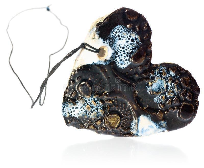 Χειροποίητος πολύχρωμος κεραμικός κοσμήματος περιδεραίων καρδιών σε ένα μίγμα των χρωμάτων μπλε, άσπρος, καφετής στοκ εικόνες