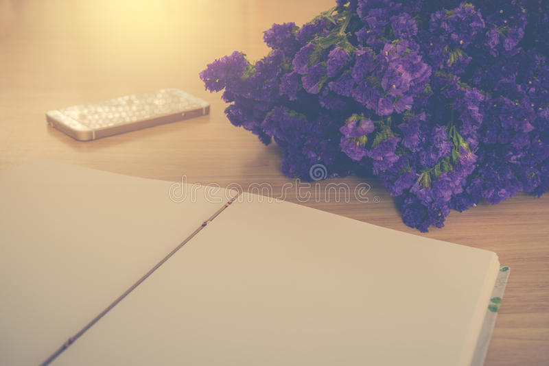 Χειροποίητο βιβλίο, κινητά τηλέφωνο και λουλούδι Statice στον ξύλινο πίνακα στοκ φωτογραφία με δικαίωμα ελεύθερης χρήσης
