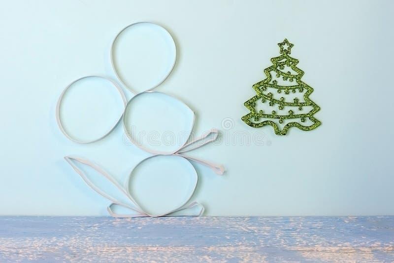 Χειροποίητο ειδώλιο ποντικιών φιαγμένο από λουρίδες του εγγράφου κοντά σε ένα πράσινο χριστουγεννιάτικο δέντρο σε ένα ανοικτό μπλ στοκ εικόνες