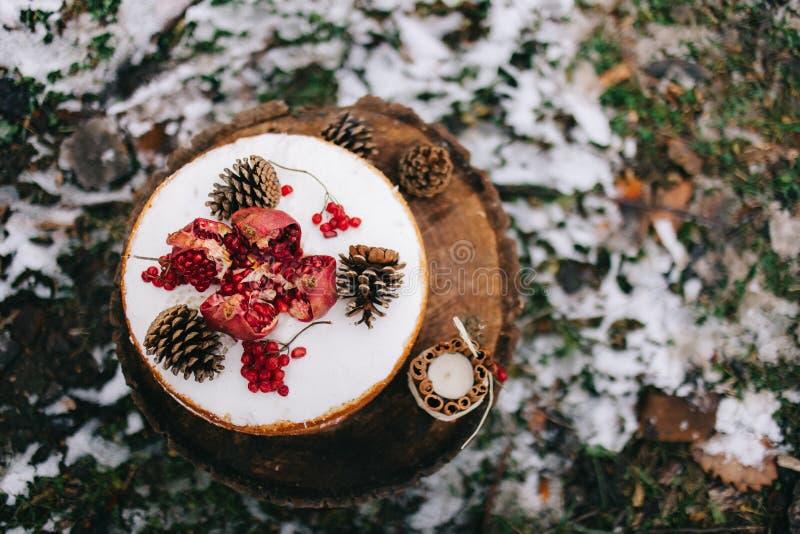 Χειροποίητο καφετί biscui tcake που διακοσμείται με τα κέικ granate και κώνων με την κρέμα στοκ φωτογραφίες