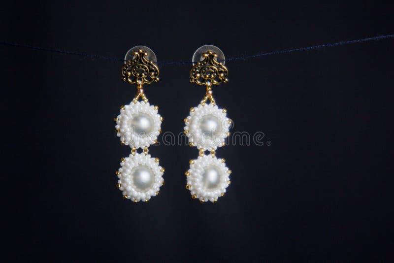 Χειροποίητο κόσμημα φιαγμένο από χάντρες στη μακροεντολή σκουλαρίκια από τις άσπρες χάντρες σκουλαρίκια από τις πέτρες Όμορφο orn στοκ φωτογραφία με δικαίωμα ελεύθερης χρήσης
