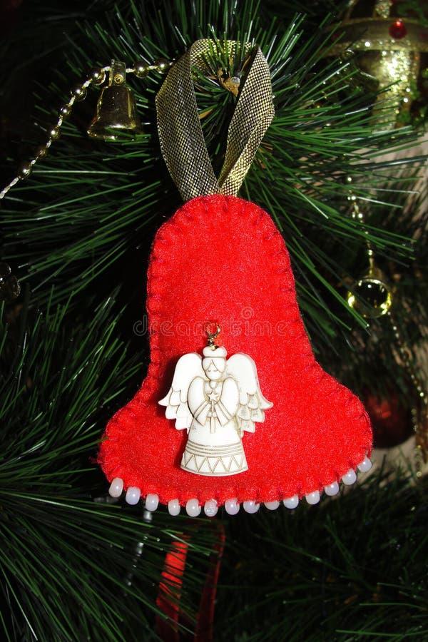Χειροποίητο παιχνίδι Χριστουγέννων σε ένα χριστουγεννιάτικο δέντρο Φωτεινό κόκκινο κουδούνι φιαγμένο από αισθητός στοκ φωτογραφίες