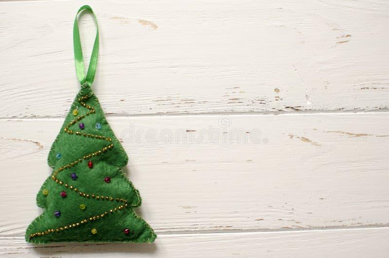 Χειροποίητο παιχνίδι χριστουγεννιάτικων δέντρων από αισθητός στο ξύλινο πνεύμα υποβάθρου στοκ εικόνα με δικαίωμα ελεύθερης χρήσης