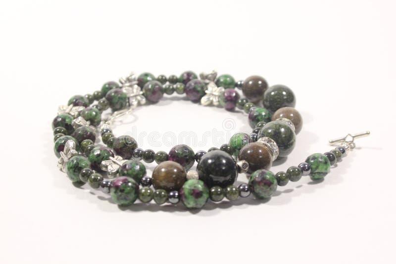 Χειροποίητο περιδέραιο του πράσινου χρώματος από τις πολύχρωμες φυσικές πέτρες σε ένα άσπρο υπόβαθρο στοκ εικόνες