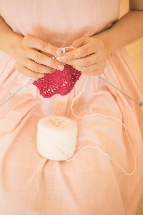 Χειροποίητο χόμπι πλεξίματος μια γυναίκα πλέκει στις βελόνες ρόδινο λευκό στοκ εικόνα